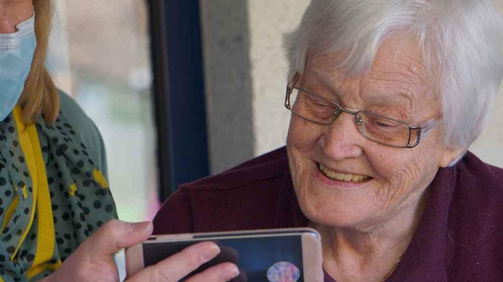 Una mujer mayor viendo un contenido en un móvil.