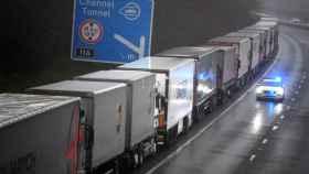 Un coche de policía pasa junto a una larga cola de camiones que permanecen atrapados a causa del cierre de la frontera con Reino Unido decretada por Francia.