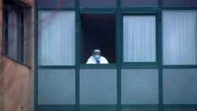 Una trabajadora sanitaria observa desde el interior de una residencia.