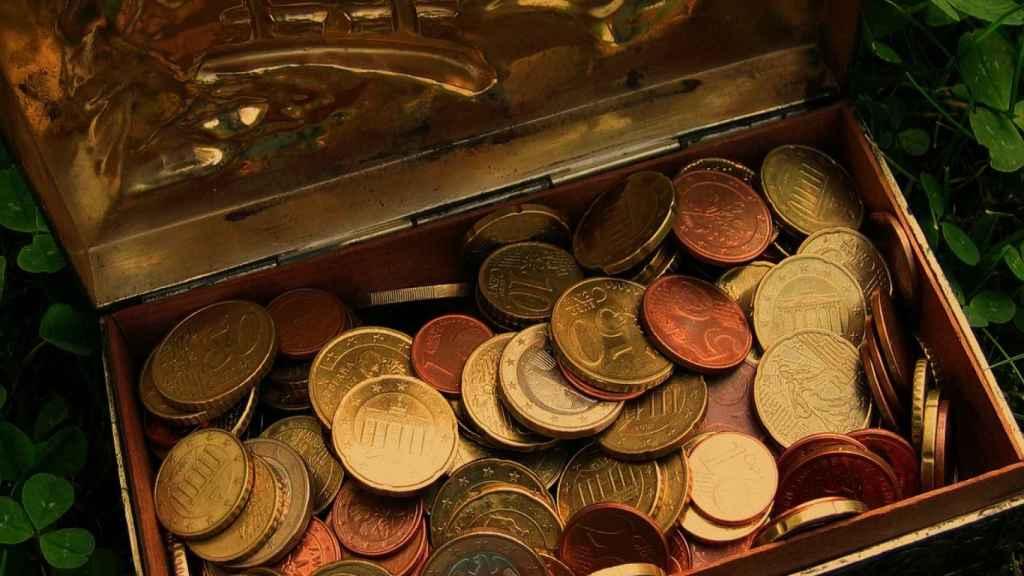 Monedas de euro en un cofre de lata.