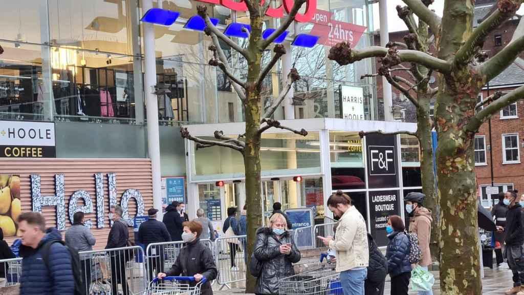 Personas haciendo cola en Londres a las afueras de un supermercado Tesco.