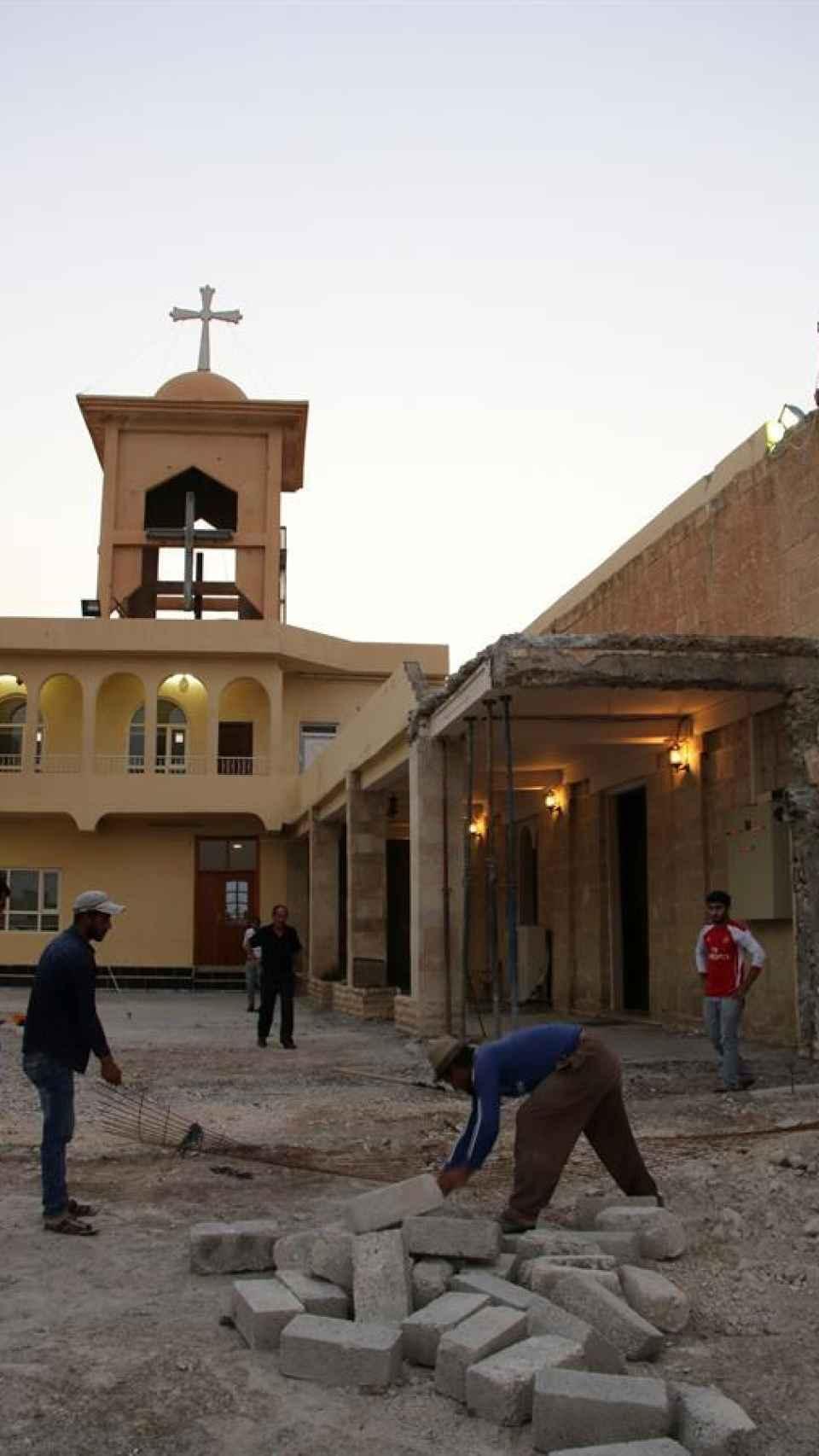Varios cristianos reconstruyen una de las iglesias destruidas por Estado Islámico en Qaraqosh.