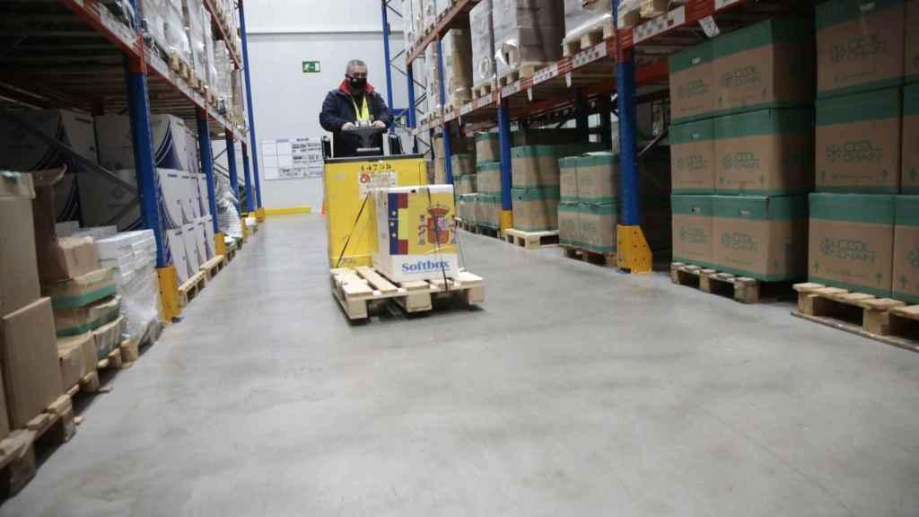 Un técnico de la Agencia Española del Medicamento y Productos Sanitarios transporta el priemr cargamento de vacunas en el almaén de Guadalajara.