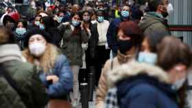Gente paseando con mascarilla por una calle de Madrid.