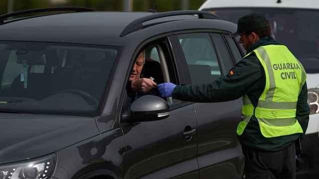 Un agente de la Guardia Civil, solicitando a un conductor su permiso de conducir.