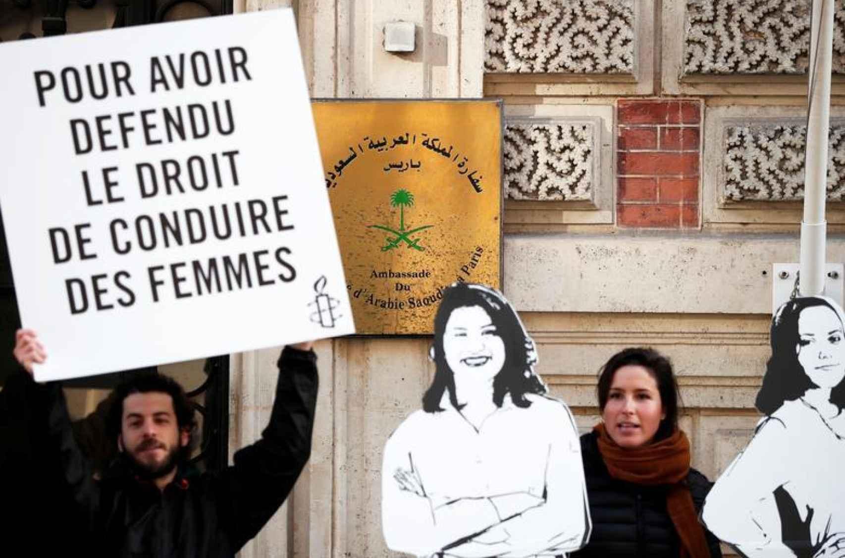 Manifestantes de Amnistía Internacional sostienen pancartas frente a la embajada de Arabia Saudita en París durante el 8-M de 2019 para protestar contra las detenciones de las activistas Loujain al-Hathloul, Eman al-Nafjan y Aziza al-Yousef.