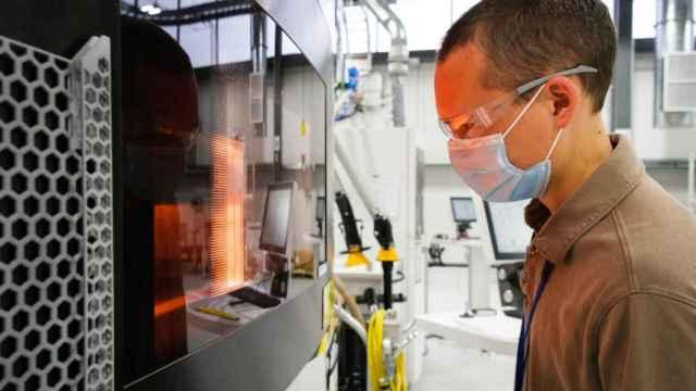 El ingeniero de General Motors Benjamin LeBlanc inspecciona una impresora 3D en el centro de fabricación aditiva.