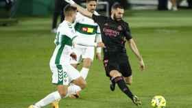 Benzema dispara a la portería del Elche presionado por un jugador rival