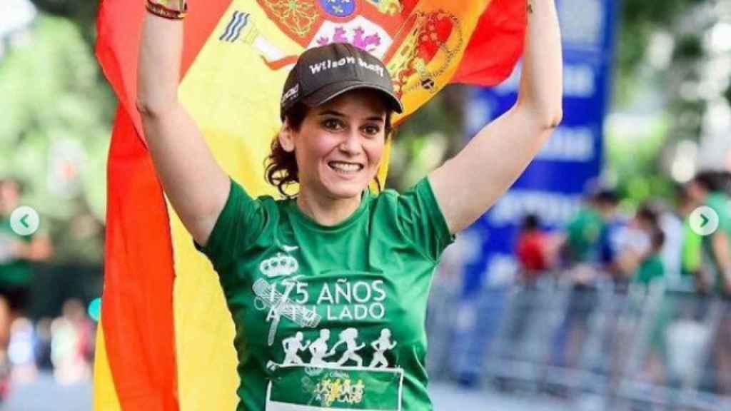 Isabel Díaz Ayuso porta la bandera de España mientras participa en una carrera.