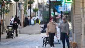 Dos personas caminando por la calle con mascarilla.