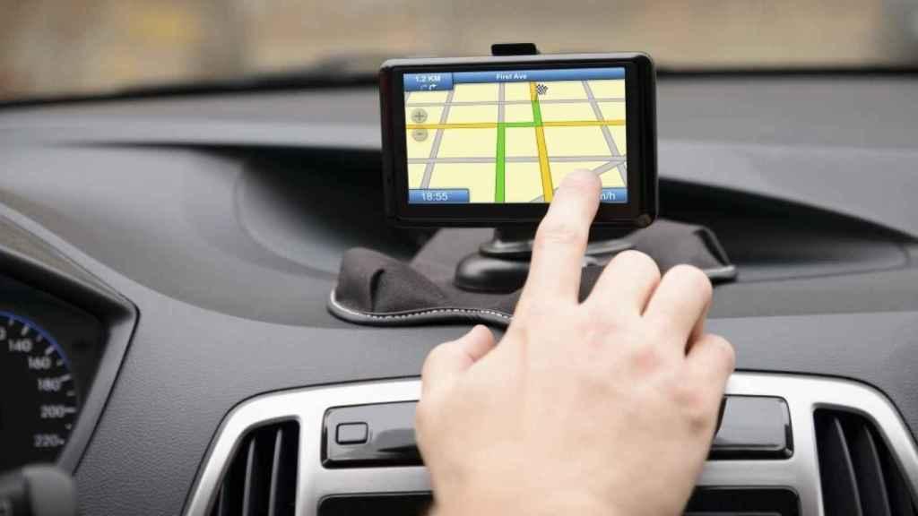 Un conductor utiliza su navegador en el coche.