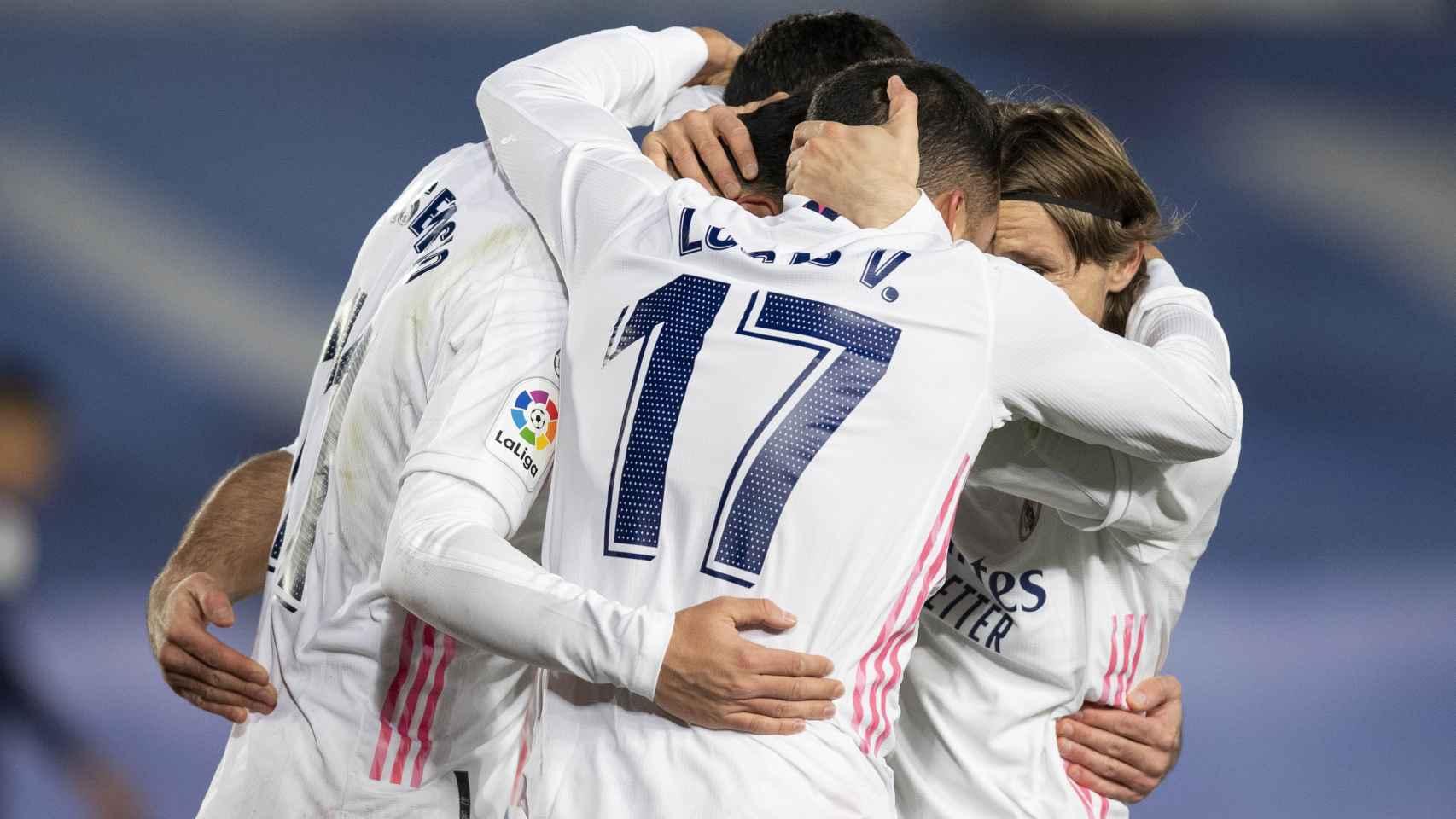 Lucas Vázquez, Marco Asensio y Luka Modric se abrazan celebrando un gol del Real Madrid