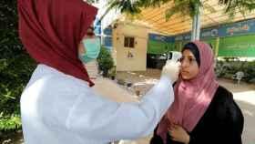 Una trabajadora sanitaria le toma la temperatura a una mujer palestina en Gaza.