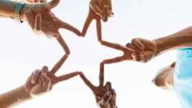 Cinco personas forman una estrella con sus manos.