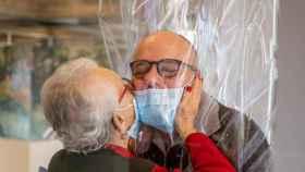 Una madre besa a su hijo a través de una lámina de plástico instalada en la 'sala de abrazos' de una residencia italiana.