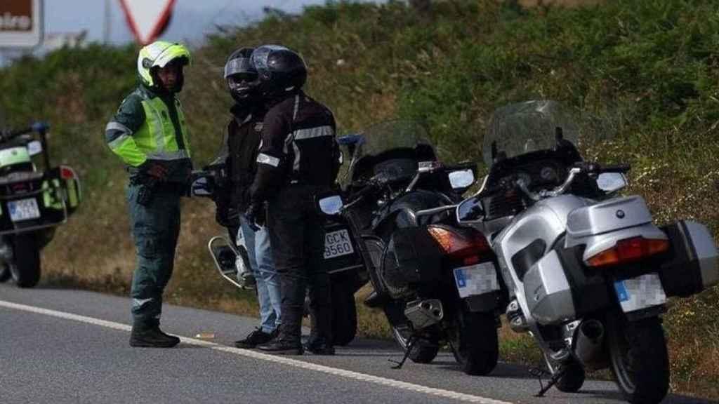 Un agente de la Guardia Civil dialoga con dos motoristas.