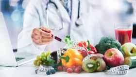 Un médico acompañado de alimentos saludables.
