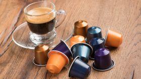 Unas cápsulas rodeando a un café recién hecho.
