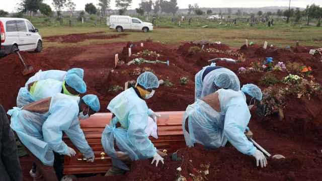 Trabajadores funerarios con EPIs entierran a una víctima fallecida por coronavirus en Joburg, Sudáfrica.