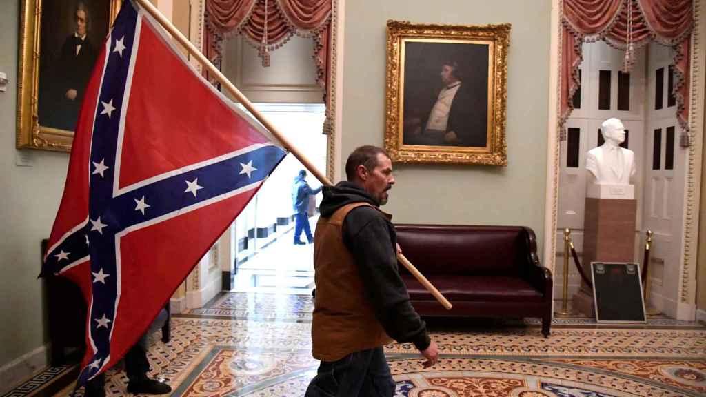 Uno de los asaltante del Capitolio, con una bandera confederada.