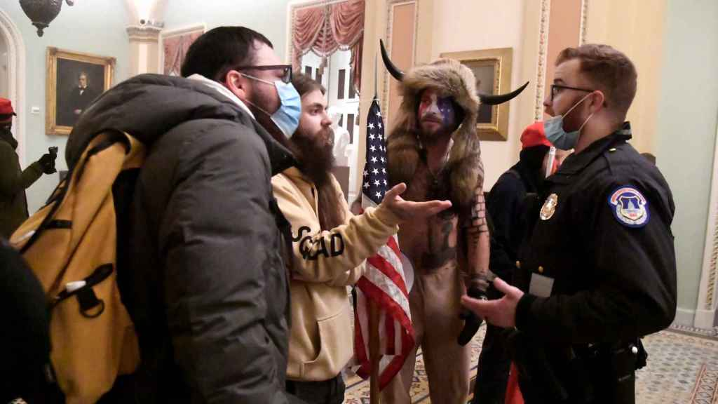 Jake Angeli, en el centro, durante la primera discusión con la policía en el interior del Capitolio.