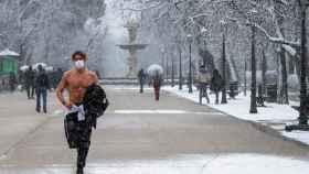 Un hombre corre por El Retiro de Madrid durante la nevada de este jueves.