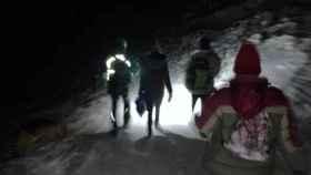 El agente (izda). y los jóvenes tras ser rescatados en plena noche.