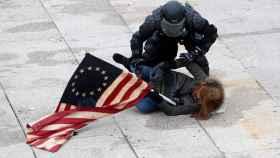 Un policía detiene a uno de los manifestantes proTrump en las puertas del Capitolio.
