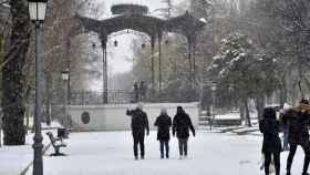 Varias personas caminan este jueves entre la nieve por el Parque Lineal de Albacete.