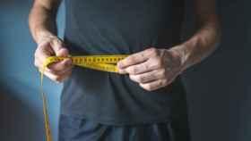 Un hombre midiéndose la cintura.