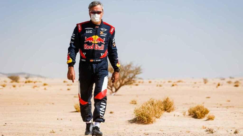 Carlos Sainz camina por la arena del desierto en el Dakar 2021