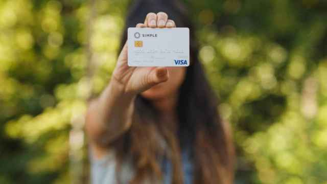 Una mujer sostiene una tarjeta de Simple, la 'fintech' que BBVA ha cerrado en Estados Unidos
