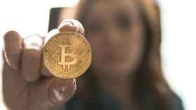 Una mujer sostiene una moneda física de bitcoin.