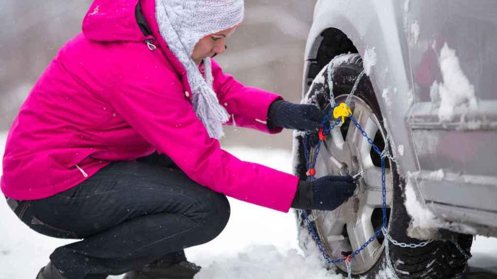 Una mujer coloca las cadenas en su coche.