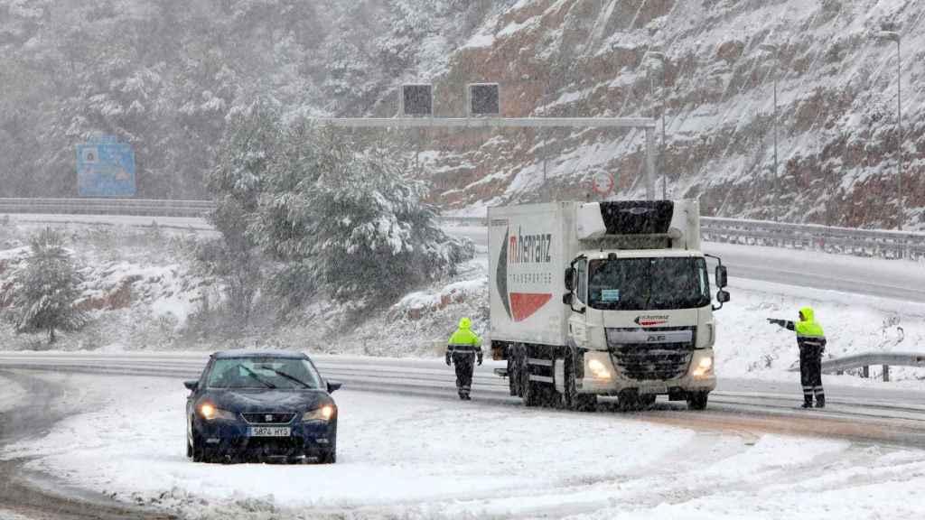 Un coche y un camión varados en una carretera cubierta por nieve.