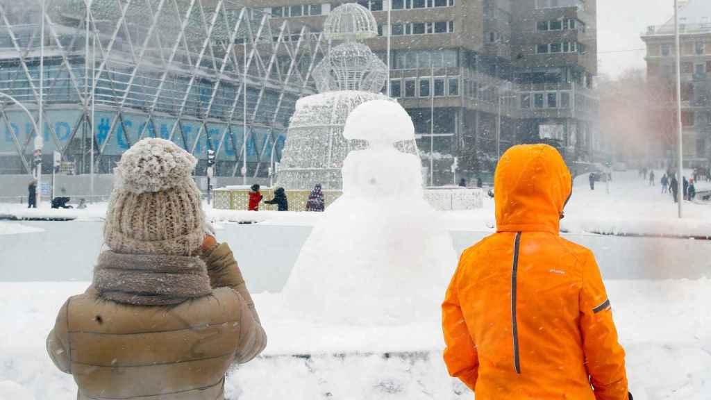 Una estatua de una menina reproducida con nieve en la Plaza de Colón en Madrid cubierta de nieve.