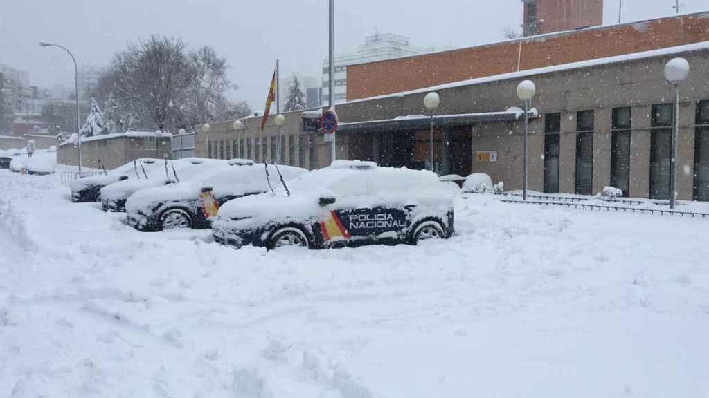 Los coches de la policía, completamente rodeados por la nieve.