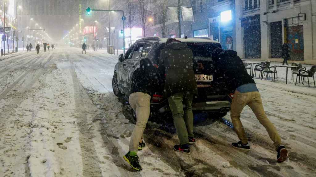 Imagen de unas personas en Madrid empujando un coche que ha perdido la tracción.