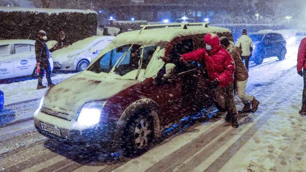 Imagen de unos usuarios ayudando a un coche en Madrid.