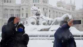 Varias personas se fotografían junto a la Plaza de Cibeles de Madrid.