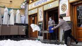Un hombre retira nieve de la entrada de un establecimiento.