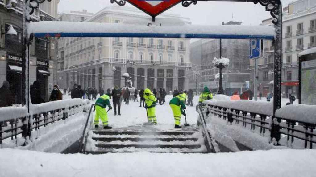 Efectivos quitando nieve en la puerta de la estación de metro de Callao, Madrid
