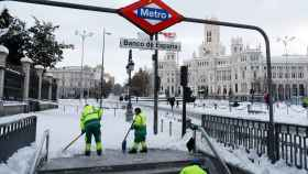 Unos operarios del Ayuntamiento de Madrid limpian la entrada a la parada de Metro de Banco de España.