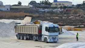 Un operario supervisando cómo las 'bañeras' de dos camiones llegados de la capital de España son cargados con sal marina de Torrevieja.