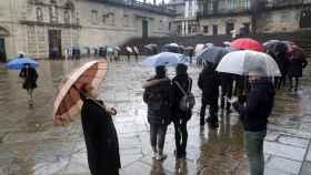Personas hacen cola para acceder a la Catedral de Santiago por la Puerta Santa portando mascarillas y guardando la distancia de seguridad.