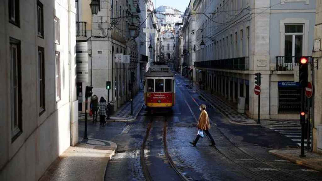 Una mujer cruzando la calle en Lisboa.