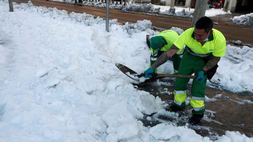 Unos operarios del Ayuntamiento de Madrid limpian la nieve acumulada en la plaza de Colón.