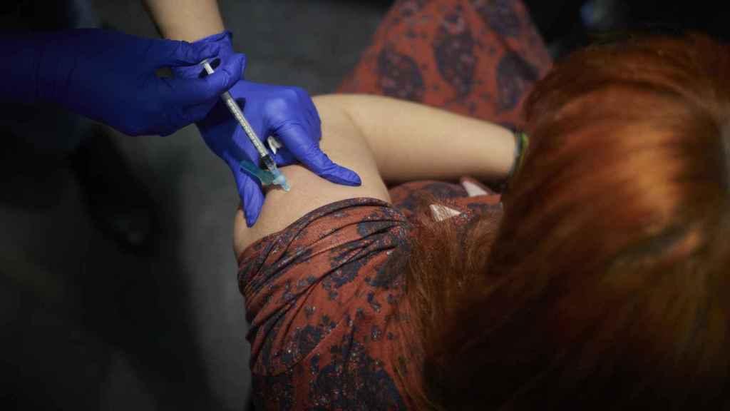 Un sanitario le pone la vacuna contra el coronavirus a una mujer.