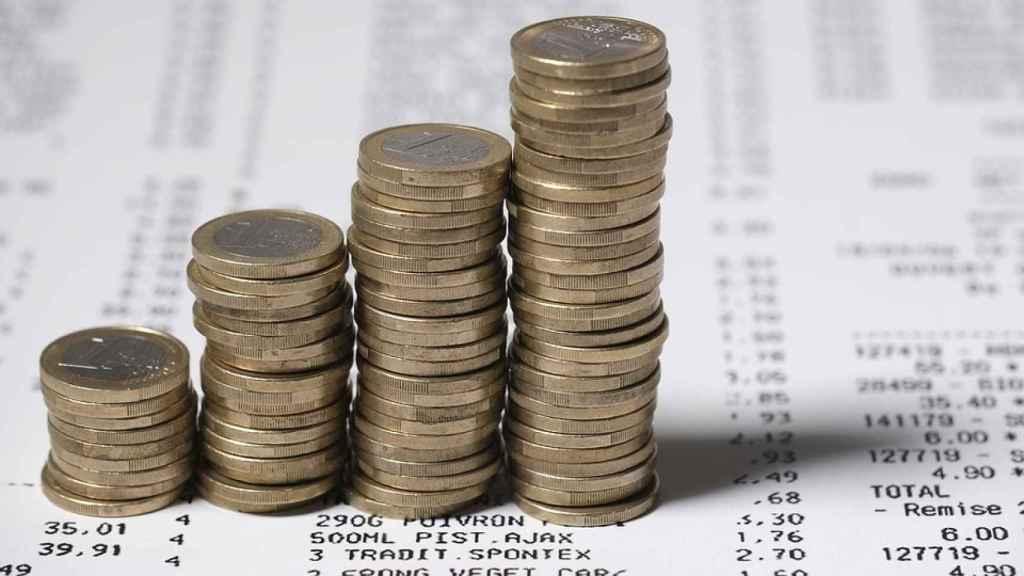 Monedas apiladas sobre registros de contabilidad.