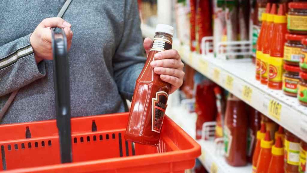 Un señor compra kétchup en el supermercado.